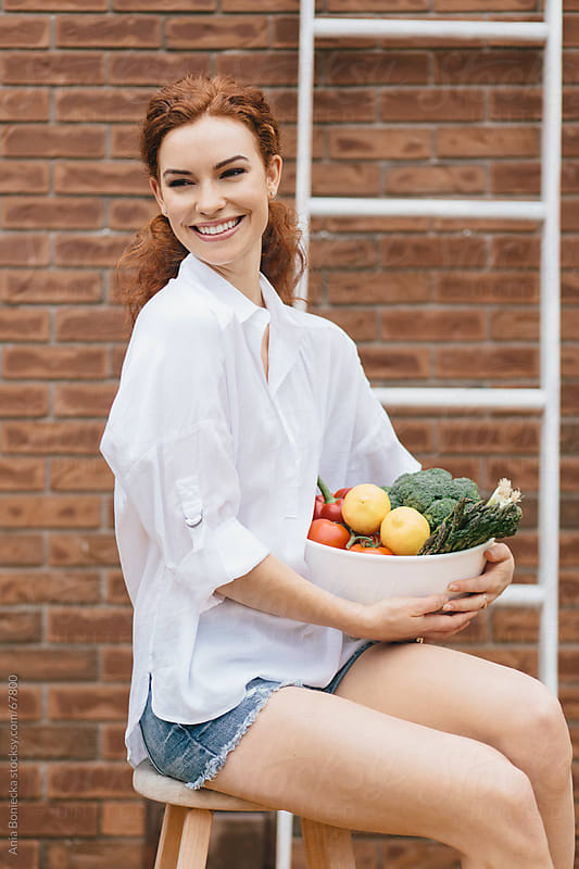 Happy beautiful redhead woman holding fresh vegetables by Ania Boniecka for Stocksy United