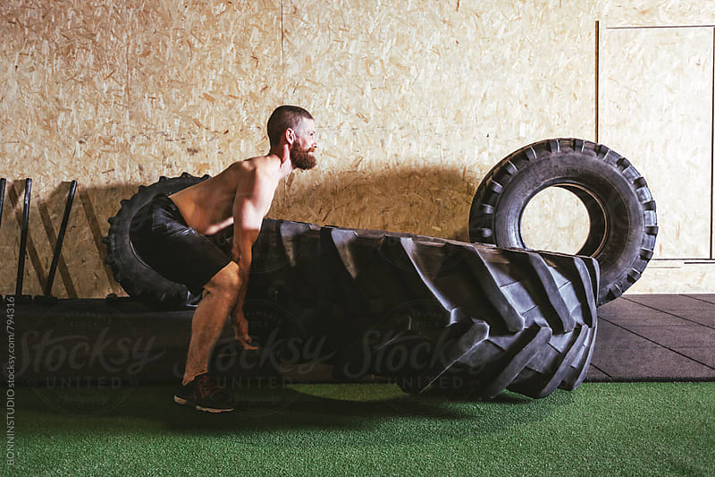Man lifting a heavy tire in a gym box. by BONNINSTUDIO for Stocksy United