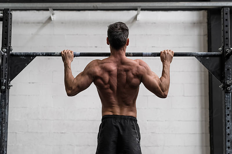 Man doing pull-ups in a gym. view from behind by Guille Faingold for Stocksy United