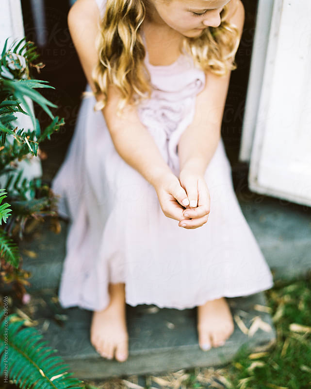 Girl sitting on porch in pink dress by Heather Perera for Stocksy United