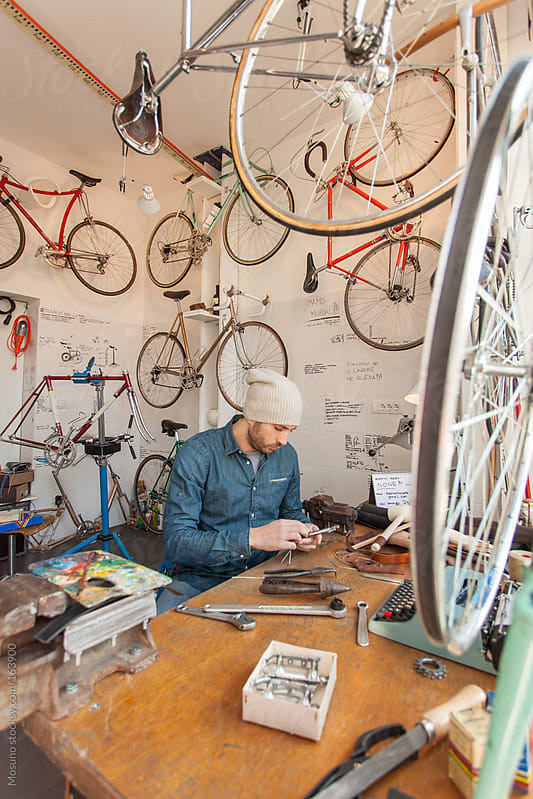 Man Working in a Bicycle Store by Mosuno for Stocksy United