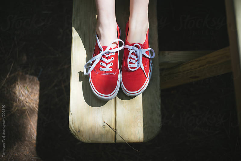 Young woman sitting on the bench with red shoes by Tommaso Tuzj for Stocksy United