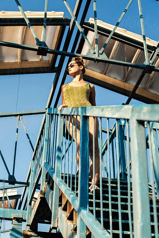 Hip female model walking downstairs on metal construction in tricot. by Audrey Shtecinjo for Stocksy United
