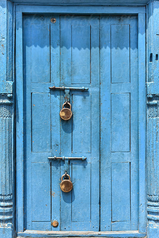 Two padlocks on a blue door by Bisual Studio for Stocksy United