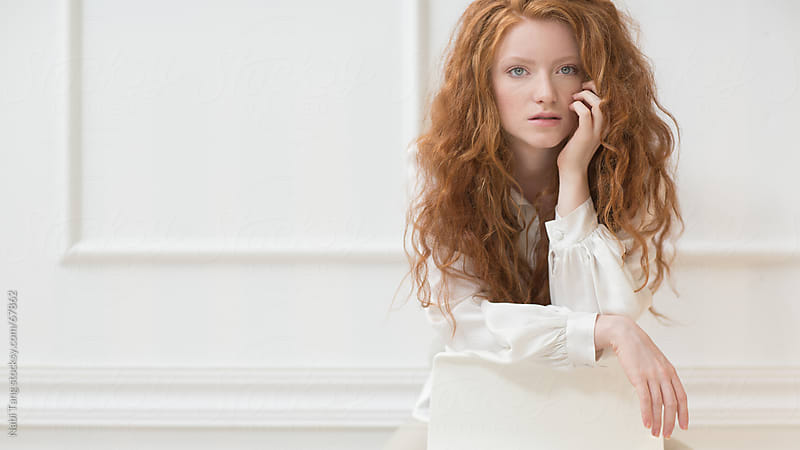 Beautiful ginger girl in front of white vintage wall by Nabi Tang for Stocksy United