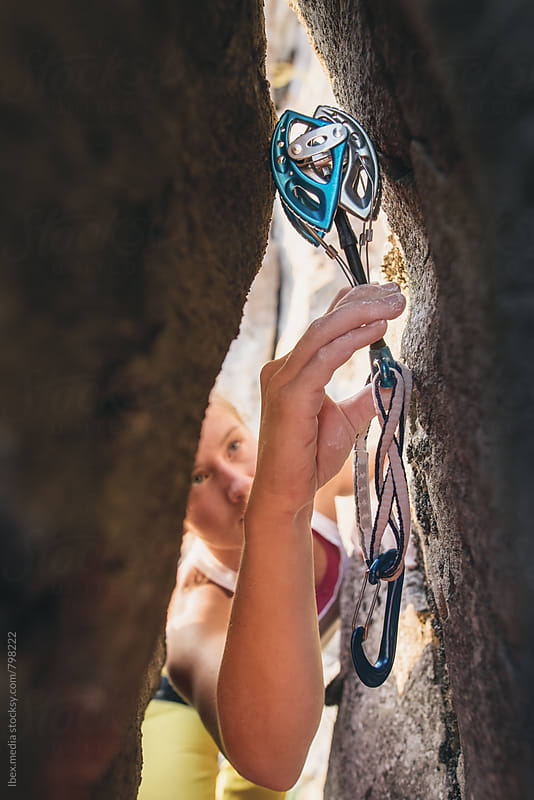 Rock climber placing climbing gear into a rock crack by RG&B Images for Stocksy United