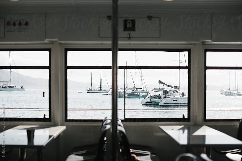 view of sailboats on water from inside of a boat by Nicole Mason for Stocksy United