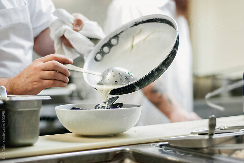 Chef pours broth over a bowl of mussels in a restaurant kitchen by Cara Dolan for Stocksy United