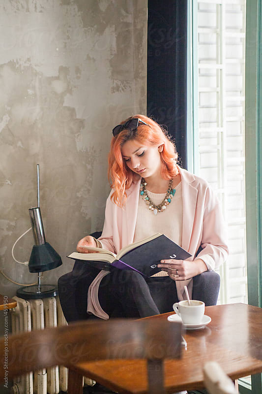 Young woman reading a book in coffee shop. by Audrey Shtecinjo for Stocksy United