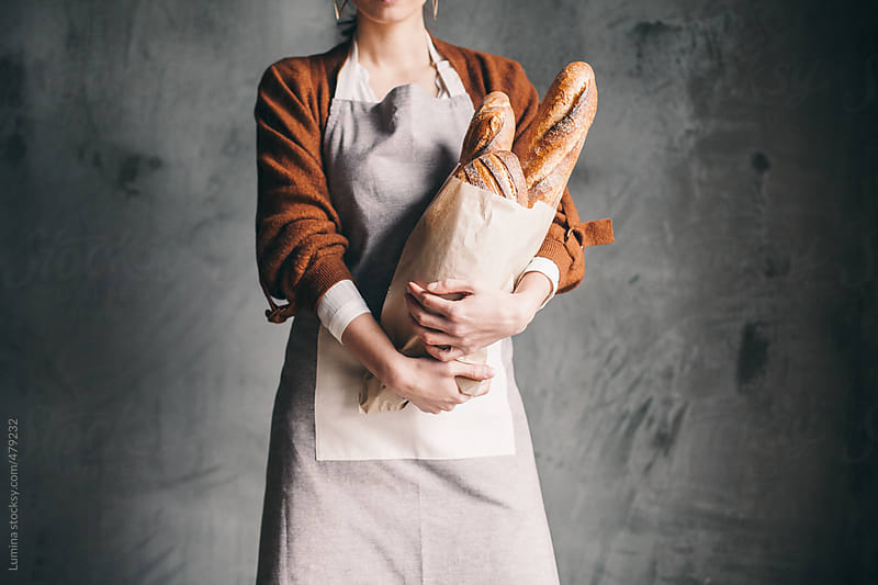 Woman Holding a Bag With Bread by Lumina for Stocksy United