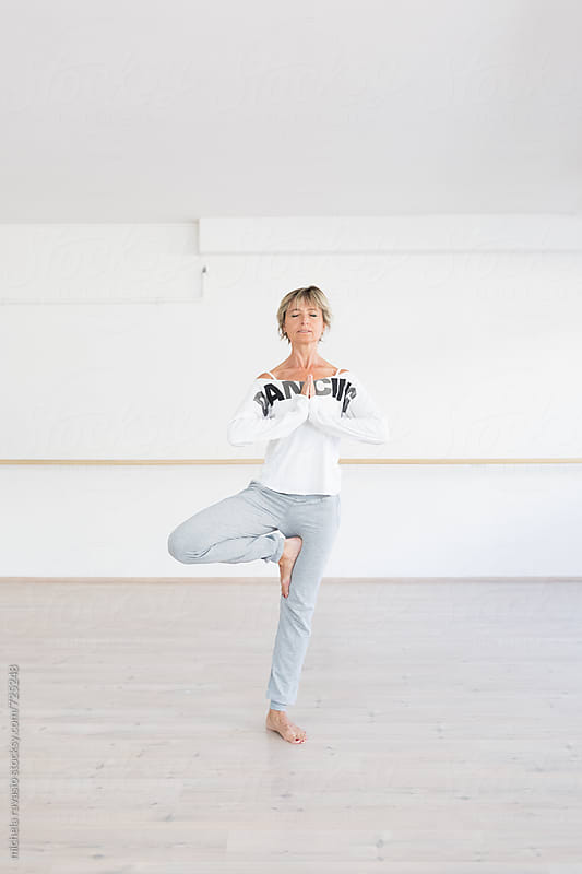Mature woman doing yoga tree pose by michela ravasio for Stocksy United