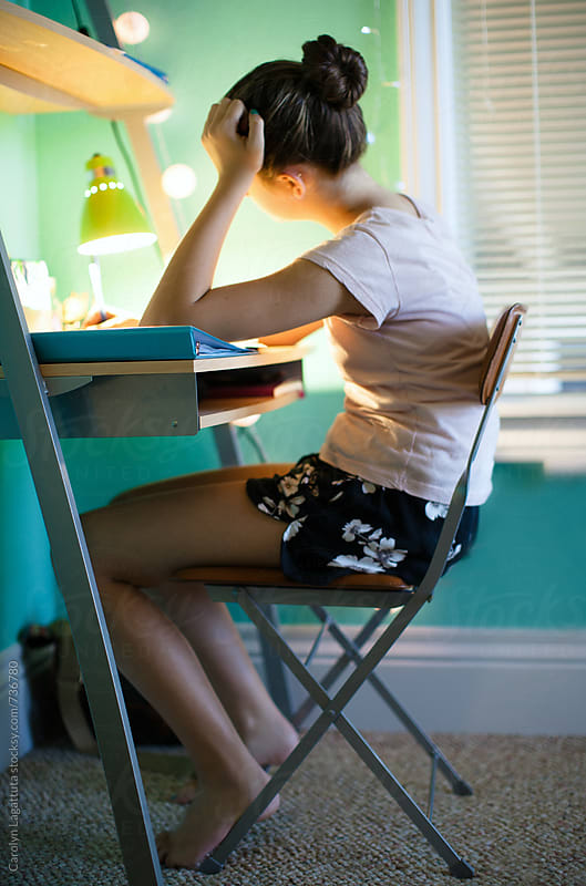 Teenage girl sitting at her desk in her bedroom doing homework by Carolyn Lagattuta for Stocksy United