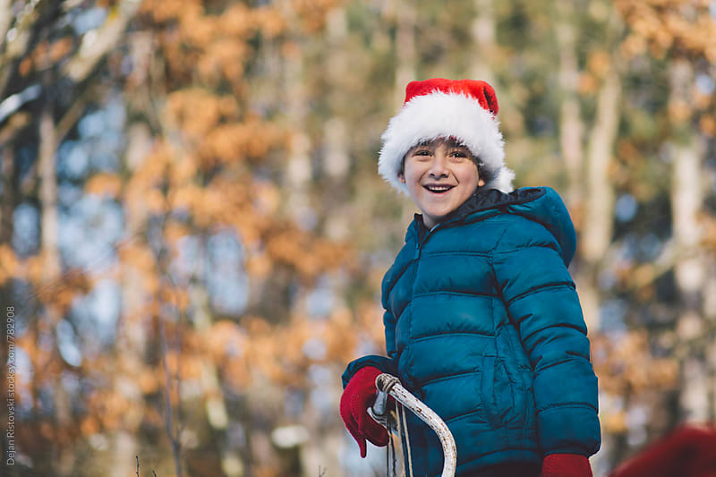 Boy with Santa hat standing in the forest. by Dejan Ristovski for Stocksy United