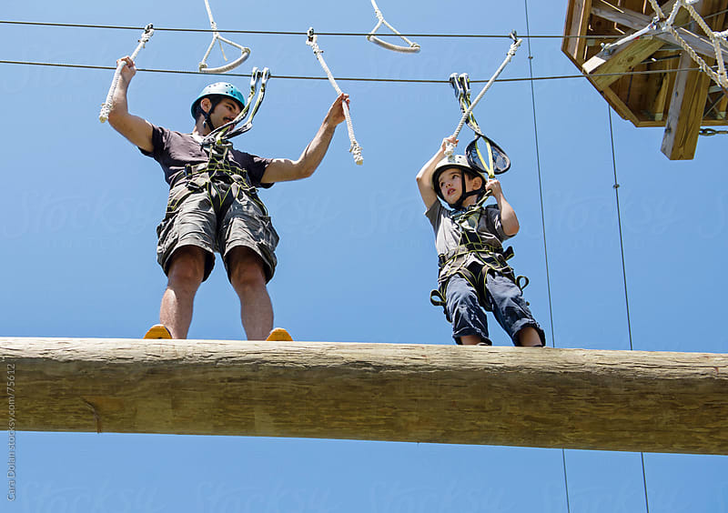 Boy and his dad climbing together on a ropes course by Cara Dolan for Stocksy United
