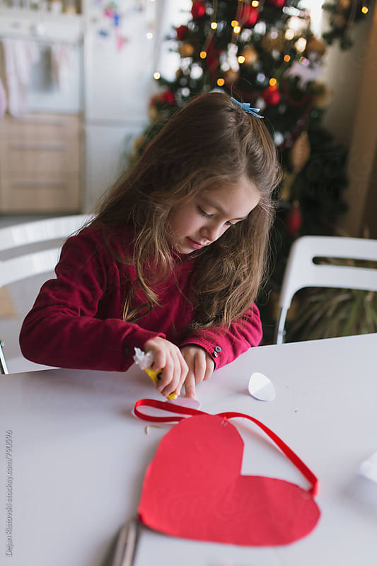 Child doing Christmas crafting at home. by Dejan Ristovski for Stocksy United