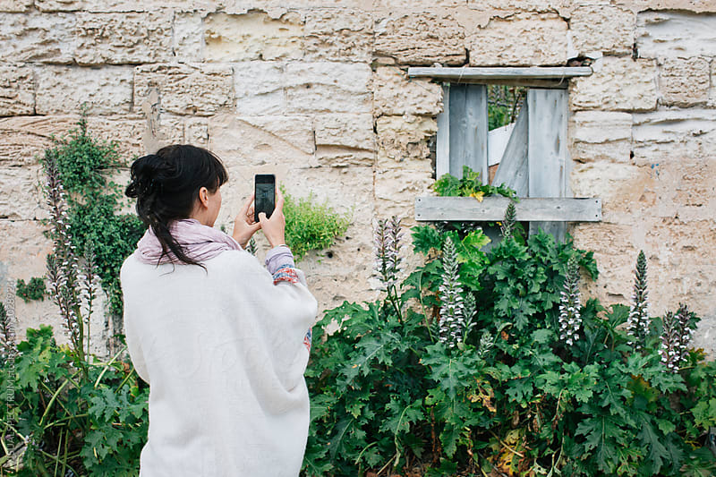 Southern Italy - Brunette in White Poncho Taking Smartphone Photo of Old Stone Wall by VISUALSPECTRUM for Stocksy United