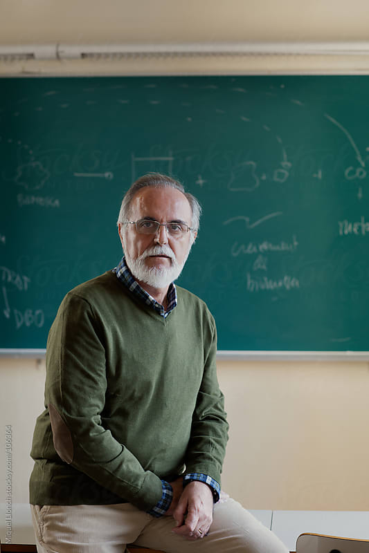 Portrait of  mature professor in a classroom with green blackboard by Miquel Llonch for Stocksy United