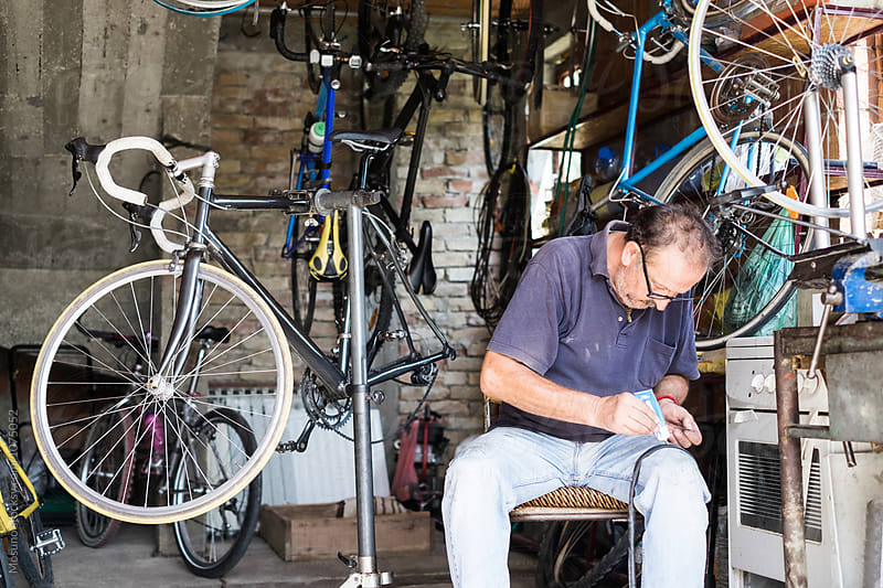 Senior Man Repairing Bicycle Tyre  by Mosuno for Stocksy United
