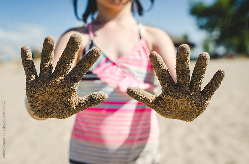Girl with sandy hands at the beach by Lindsay Crandall for Stocksy United