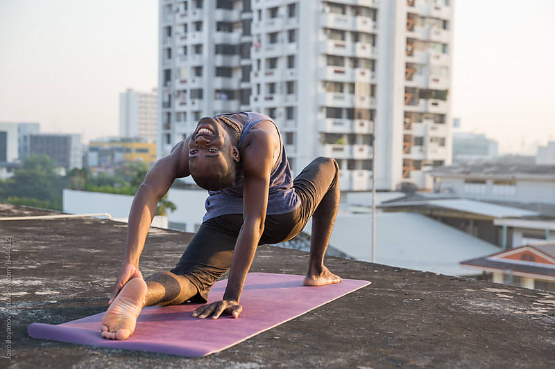 Handsome and fit young man doing yoga on a city rooftop  by Jovo Jovanovic for Stocksy United