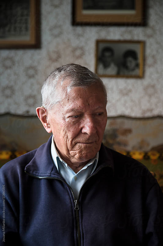 Portrait of a senior man having hearing aid in his ears by Jovana Milanko for Stocksy United