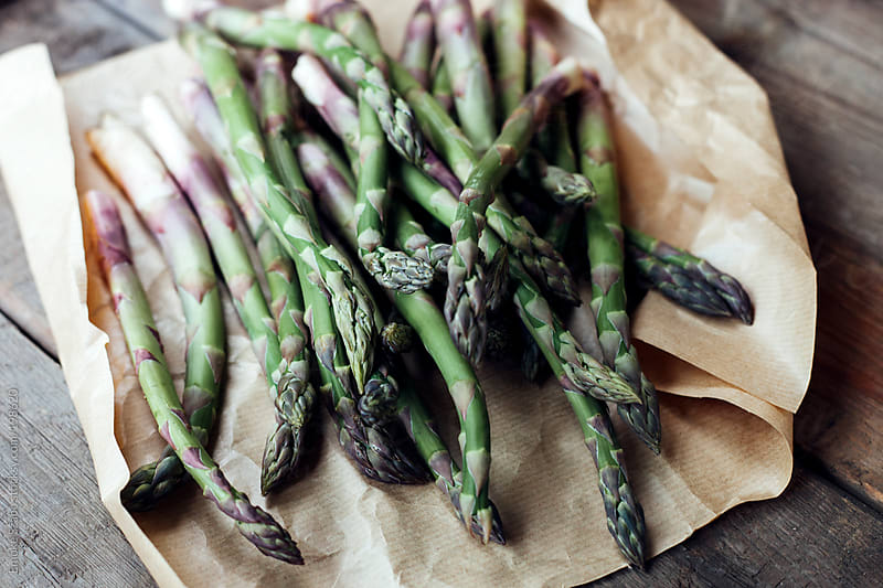 Fresh asparagus on brown paper on wooden board by Emoke Szabo for Stocksy United