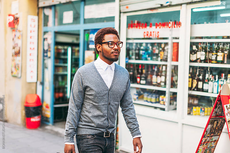 Black man on the street in front a liquor store.  by BONNINSTUDIO for Stocksy United