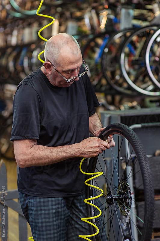 Local Bike Shop: Store Owner Inflates Bicycle Tire by Brian McEntire for Stocksy United