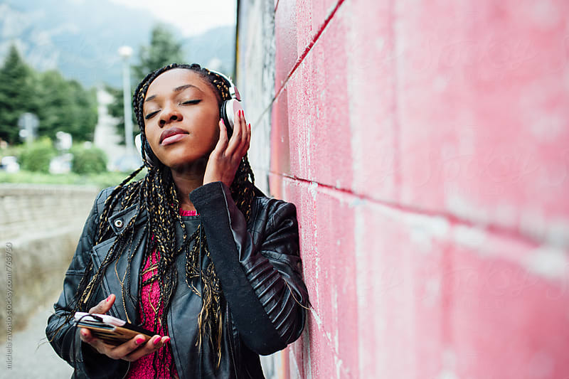 Young woman wearing headphones with eyes closed by michela ravasio for Stocksy United