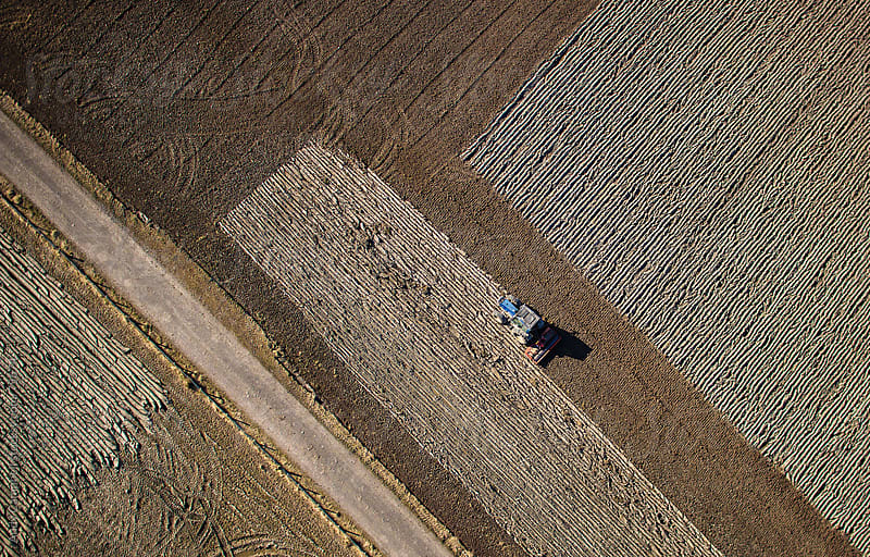 Aerial view of farmland with a tractor plowing a field's soil by Andy Campbell for Stocksy United