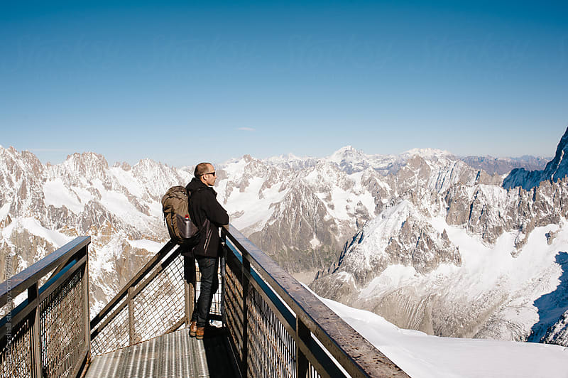 Man standing on a walkway at Aiguille du Midi looking at the Mont Blanc Massif mountains by Suzi Marshall for Stocksy United