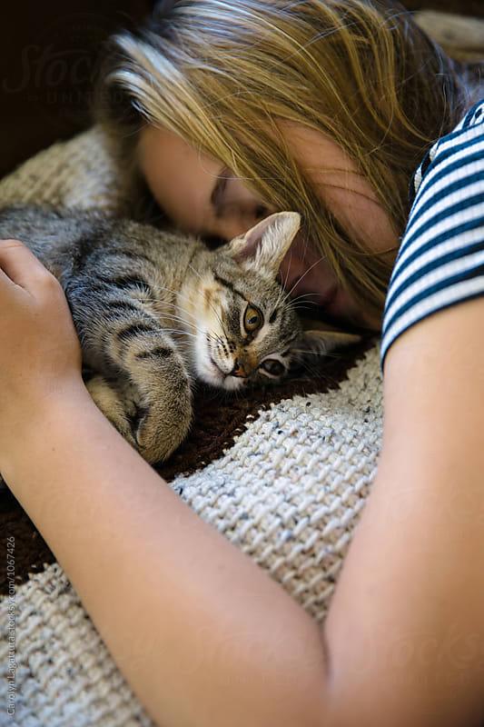 Teenage girl sleeping with her kitten by Carolyn Lagattuta for Stocksy United