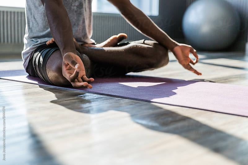 Closeup of a man meditating in a bright and modern yoga studio  by Jovo Jovanovic for Stocksy United