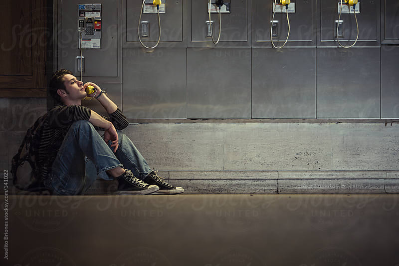 Young Man Talking on a Public Phone by Joselito Briones for Stocksy United