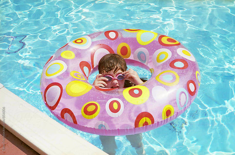 film image of young girl floats in pool with pool toy by Tana Teel for Stocksy United