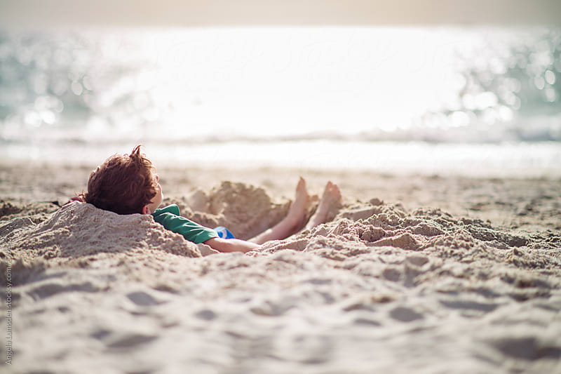 Boy relaxing in the sand at the beach by Angela Lumsden for Stocksy United