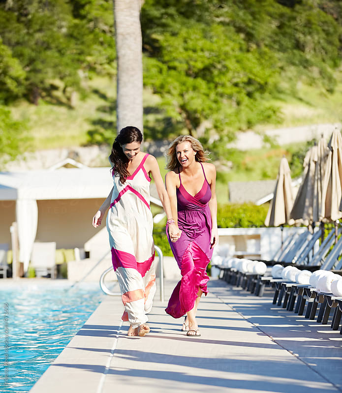 Girlfriends having fun together at luxury resort pool  by Trinette Reed for Stocksy United