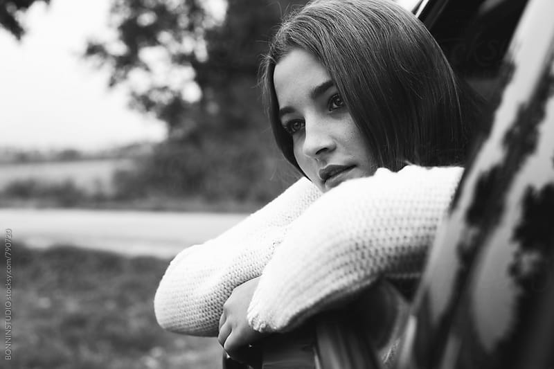 Teen girl in a car ride. Black and white photo. by BONNINSTUDIO for Stocksy United