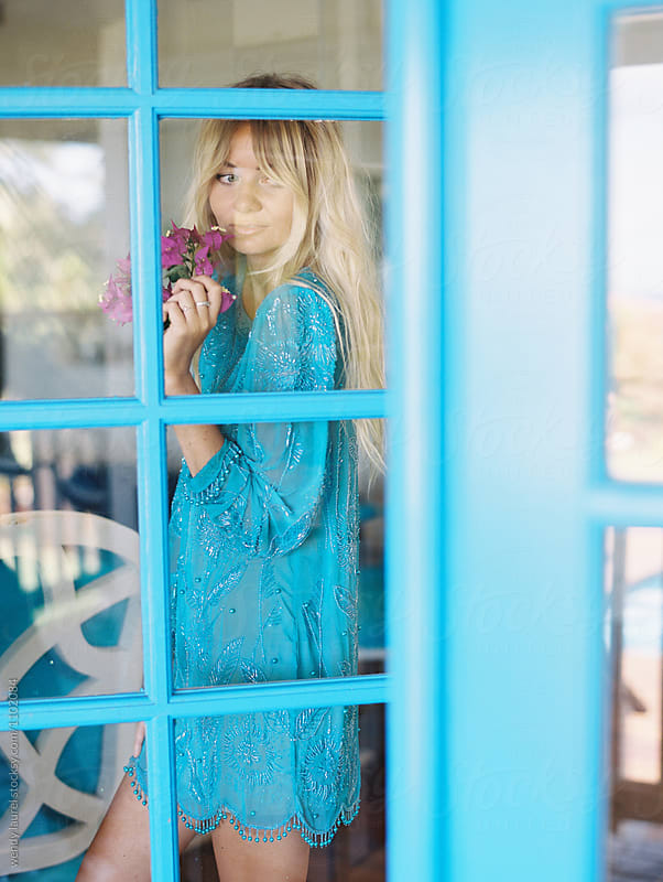 blonde girl through blue door by wendy laurel for Stocksy United