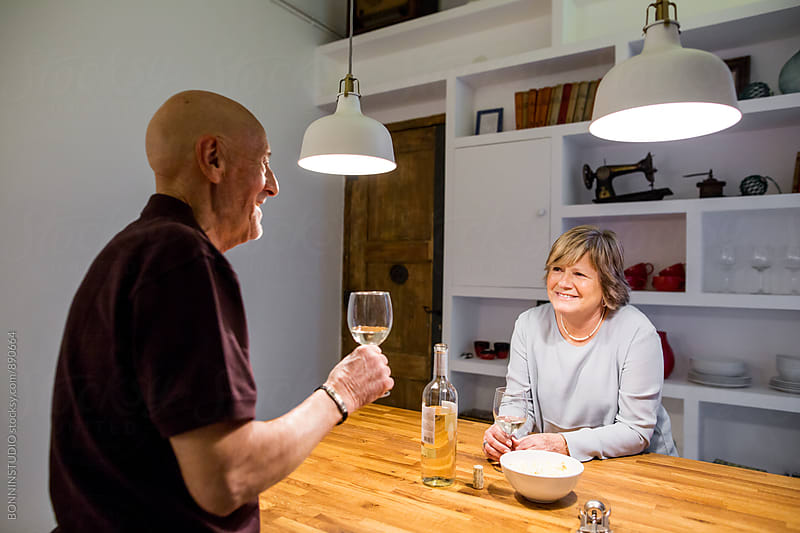 Elderly couple drinking white wine in the kitchen. by BONNINSTUDIO for Stocksy United
