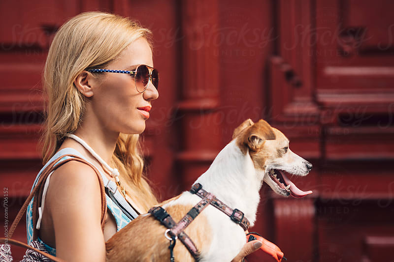 Smiling Blonde Woman Holding Her Dog by Lumina for Stocksy United