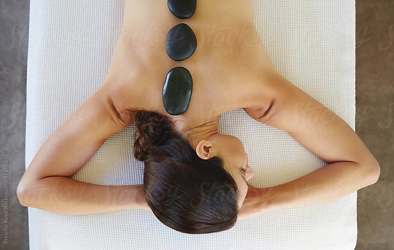 Woman receiving hot stone massage at luxury spa by Trinette Reed for Stocksy United