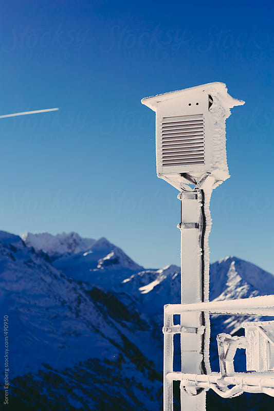 Weather station in the mountains against a blue sky in winter with flight trails and copyspace by Soren Egeberg for Stocksy United