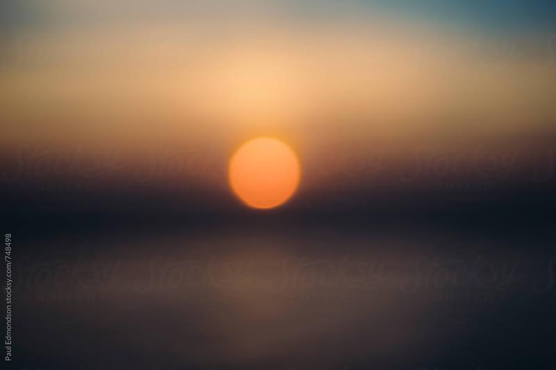 Sunset over calm ocean, blurred focus by Paul Edmondson for Stocksy United
