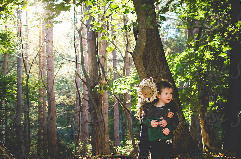 Two kids hugging in the forest by Lindsay Crandall for Stocksy United