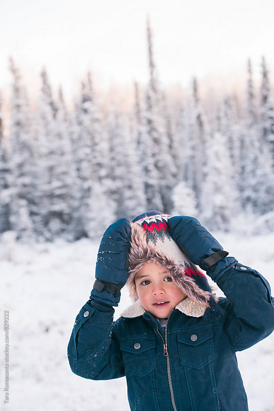 young child holding his winter hat up so he can see by Tara Romasanta for Stocksy United