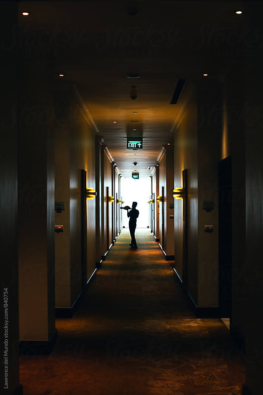 Silhouette of a waiter delivering room service in a hotel by Lawrence del Mundo for Stocksy United
