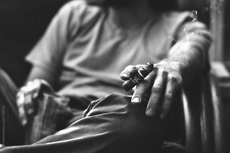 man holding cigar by Jess Lewis for Stocksy United