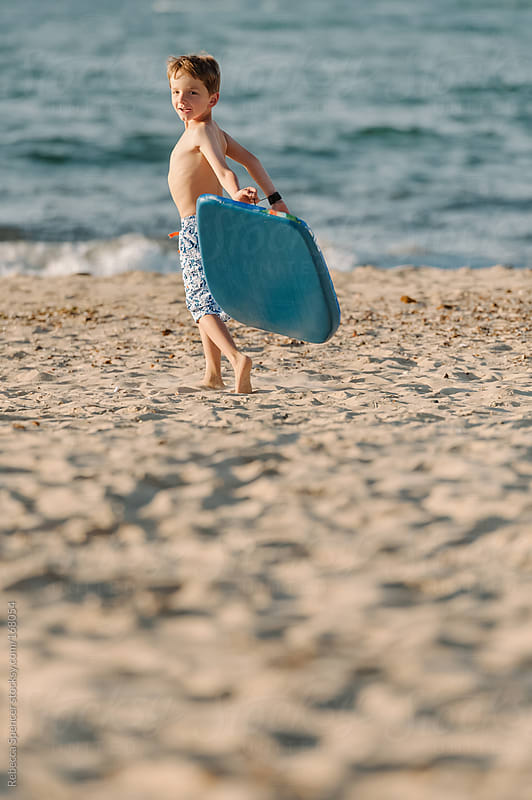 Boy holding surf board on beach looking at camera by Rebecca Spencer for Stocksy United