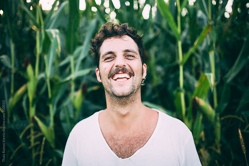 man laughting in a corn plantation  by Thais Ramos Varela for Stocksy United